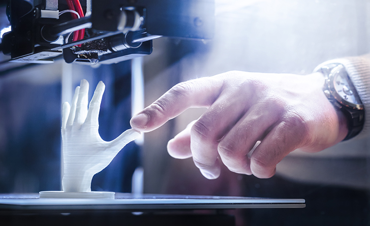 Person Using a 3D Printer to Create a Human Hand Model